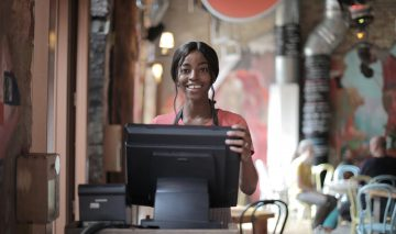 A woman stands working at the register in front of a cafe