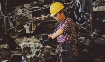 A woman in a helmet working on large machinery